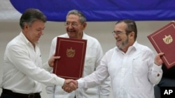 FILE - Colombian President Juan Manuel Santos, left, and Commander of the Revolutionary Armed Forces of Colombia, Timoleon Jimenez, right, shake hands during a signing ceremony of a cease-fire, June 23, 2016.