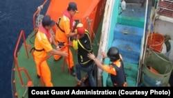 Pengawas pantai Taiwan dan salah satu awak Indonesia yang ditahan dikawal keluar dari kapal.
