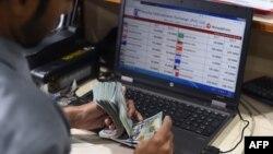 کراچی میں ایک کرنسی ایکسچینج ڈیلر امریکی ڈالر گن رہا ہے۔ (فائل فوٹو)
