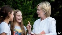 Hillary Clinton habla con jóvenes mientras firma un autógrafo luego de un evento de recaudación de fondos para su campaña presidencial en una residencia privada en Sagaponack, N.Y., el 30 de agosto.