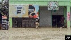 Seorang warga membersihkan lumpur dari di luar kiosnya di daerah Alcantara, propinsi Cebu, Filipina (30/12).