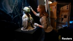"Nicole Manis, of the Lucas Museum of Narrative Art, unpacks a Yoda puppet, Nov. 8, 2016, used in the sci-fi movies. The ""Star Wars Identities"" exhibition begins next week in London."