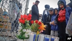 Rev. Kirsten Foy, National Action Network's north east regional director, center, with his sons, Seth, 7, far right, and and Samuel, 5, second from right, pray at a memorial, April 5, 2018, in New York, where Saheed Vassell was shot.
