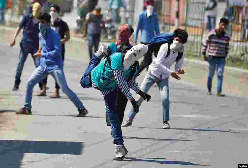 Masked Kashmiri protesters throw stones towards Indian security personnel during a demonstration against the plan to resettle Hindus in the valley, according to local media, in Srinagar.