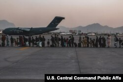 FILE - Evacuees wait to board a Boeing C-17 Globemaster III during an evacuation at Hamid Karzai International Airport, Kabul, Afghanistan, Aug. 23. (US Marine Corps photo)