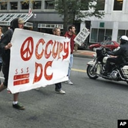 A police on a motorcycle passes a group of Occupy DC protesters as they march from McPherson Square to a Bank of America on K Street in Washington, October 20, 2011.
