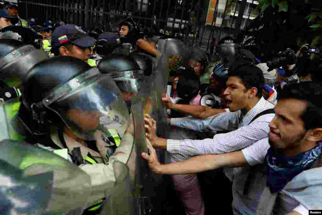 Opposition supporters confront riot security forces while rallying against President Nicolas Maduro in Caracas, Venezuela.