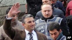 Nedim Sener, a leading investigative reporter of daily newspaper Milliyet, waves after police detained him in Istanbul, Turkey, Thursday, March 3, 2011. Police detained about 10 people, mostly journalists, including Sener, in a crackdown on an alleged sec