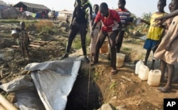 FILE - Displaced people draw water from a hole dug in the ground, in the United Nations camp for displaced people in the capital Juba, South Sudan, Jan. 19, 2016.