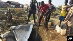 Displaced people draw water from a hole dug in the ground in the United Nations camp for displaced people in the capital Juba, South Sudan, Jan. 19, 2016.