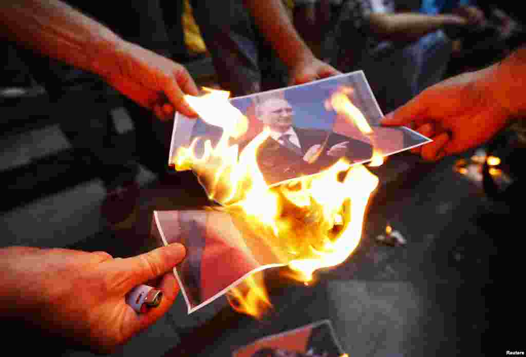Protesters burn portraits of Russian President Vladimir Putin during a rally in support of Ukraine in Tbilisi, Georgia.