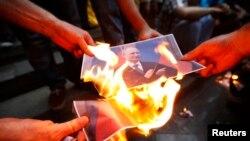 Para pengunjuk rasa membakar potret Presiden Rusia Vladimir Putin dalam sebuah unjuk rasa mendukung Ukraina di Tbilisi, Georgia. 29/8/2014.