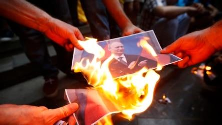 Người biểu tình đốt ảnh chân dung của Tổng thống Nga Vladimir Putin trong cuộc biểu tình ủng hộ Ukraine ở Gruzia.