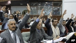 Members of Yemen's Parliament raise their hands to vote in favour of a law granting immunity to outgoing President Ali Abdullah Saleh over the killing of protesters, in Sana'a, January 21, 2012. The Parliament approved a law on Saturday granting Saleh imm