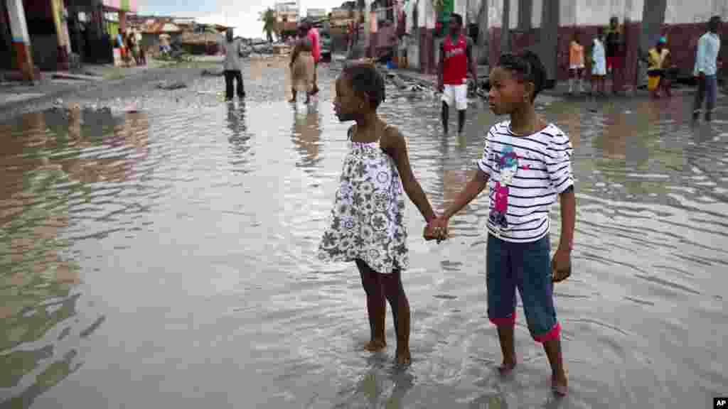 Les filles se tiennent les mains dans une rue inondée après le passage de l'ouragan Matthew à Les Cayes, en Haïti, le 6 octobre 2016.