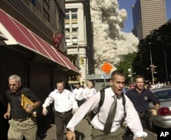 FILE - People run from a cloud of debris from the collapse of a World Trade Center tower in New York, Sept. 11, 2001.