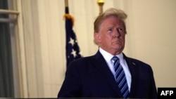 ប្រធានាធិបតីសហរដ្ឋអាមេរិកលោក Donald Trump ឈរនៅមុខសេតវិមាន បន្ទាប់ពីលោកបានចាកចេញពីមន្ទីរពេទ្យយោធា Walter Reed ត្រឡប់ទៅសេតវិមានវិញ កាលពីថ្ងៃទី ៥ ខែតុលា ឆ្នាំ២០២០។