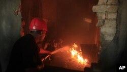 Pakistanski vatrogasac gasi požar u fabrici u Lahoreu, u utorak 11. septembra 2012.