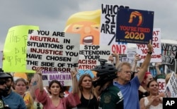 Protestors hold up anti President Donald Trump signs during a rally, June 18, 2019, in Orlando, Florida.