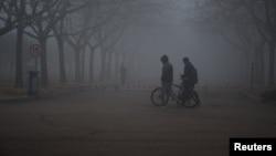 중국 산둥성 칭다오 시에 덮힌 스모그 사이로 시민들이 걷고 있다.