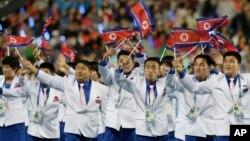 지난 4일 인천 아시안게임 폐막식에서 북한 선수단이 인공기를 흔들며 경기장으로 들어서고 있다.