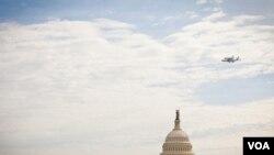 Pesawat ulang-alik antariksa Discovery melakukan penerbangan 'victory lap' di Washington, DC. Dalam foto ini terlihat terbang melintasi Gedung Capitol (foto: VOA/Alison Klein).