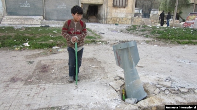 A child looks at the tail fin of a Russian-made RBK bomb that crashed through a sidewalk in a densely populated neighborhood east of Aleppo's city center, March 1, 2013.