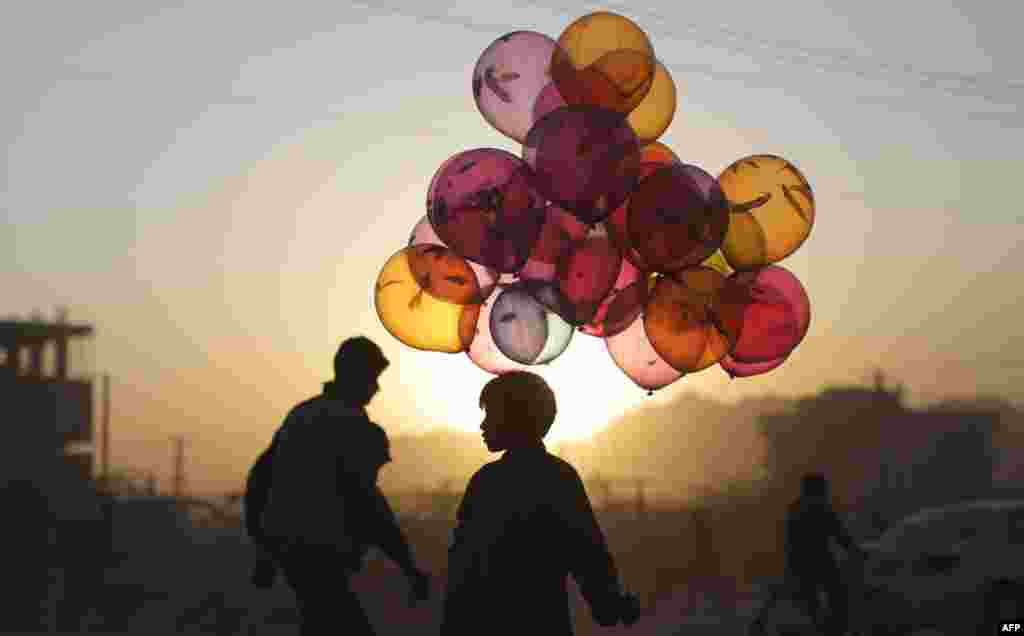 October 18: Afghan boy Mahfouz Bahbah, 12, stands on a roadside hoping to sell his balloons during sunset in Kabul, Afghanistan. AP Photo/Muhammed Muheisen)