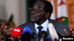 FILE: Zimbabwe's President Robert Mugabe addresses a media conference at State house in Harare, July 30, 2013.