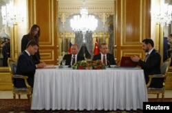 FILE - Russian Energy Minister Alexander Novak (L) and his Turkish counterpart Berat Albayrak sign an agreement in Istanbul, Turkey, Oct. 10, 2016.