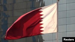 FILE - Qatar's flag flies in front of the Qatar National Bank's head office building in Doha, Nov. 30, 2009.