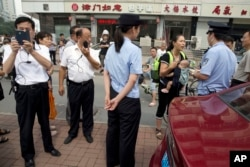 Yuan Shanshan, third right, the wife of detained Chinese lawyer Xie Yanyi, carries her child as she talks to a police officer while other plain clothes security personnel film journalists near the Tianjin No. 2 Intermediate People's Court in northern China's Tianjin Municipality on Tuesday, Aug. 2, 2016.
