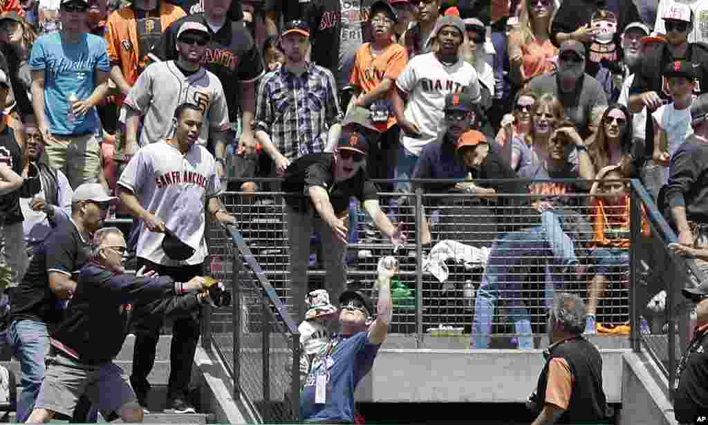 A fan holding a child, bottom, catches Colorado Rockies' Troy Tulowitzki's two-run home run against the San Francisco Giants during the third inning of a baseball game in San Francisco, June 15, 2014. The Rockies won 8-7.
