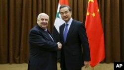 Ngoại trưởng Syria Walid al-Moualem bắt tay Bộ trưởng Ngoại giao Trung Quốc Vương Nghị trước cuộc gặp ở Bắc Kinh hôm 24/12.