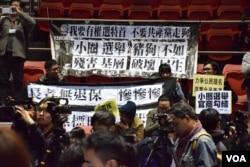示威者在記者會舉行期間在座位上掛起抗議棋額。(美國之音湯惠芸攝)