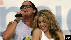 "FILE - Colombian singers Shakira, right, and Carlos Vives perform during a ""concert for peace"" Independence Day celebrations in Leticia, Colombia."