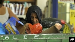 A woman collects goods from a garbage bin outside a supermarket in Thessaloniki, Greece, July 3, 2012.