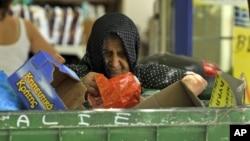 Một phụ nữ tìm những gì có thể nhặt được trong thùng rác bên ngoài một siêu thị ở Thessaloniki, Hy Lạp