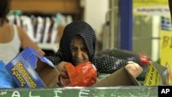 Žena skuplja hranu iz kante za djubre u Solunu