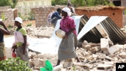 FILE: A woman salvages some bricks from her home after it was demolished by a bulldozer, Harare, Tuesday, Oct. 16, 2012. (AP Photo/Tsvangirayi Mukwazhi)