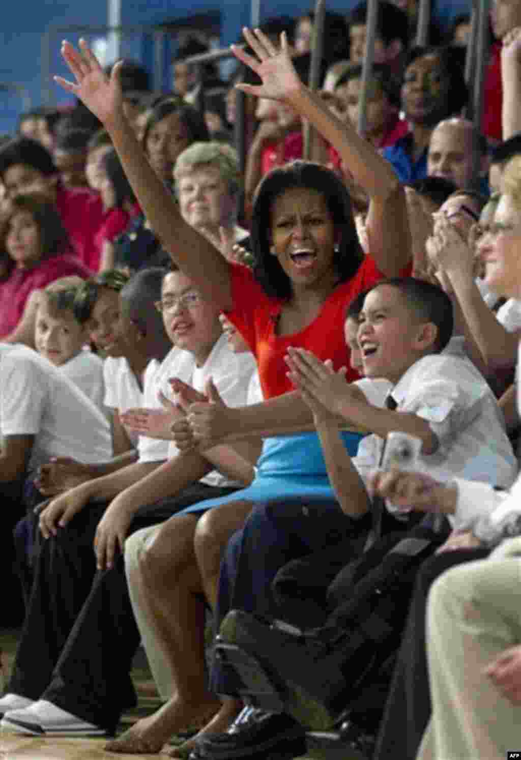 "First lady Michelle Obama cheers with students from Nancy Moseley Elementary School during a Let's Move event with members of Bravo's series ""Top Chef"" Friday, Feb. 10, 2012, at Kleberg Rylie Recreation Center in Dallas, during her three day national tour"