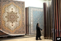 FILE - An Iranian female customer looks at the carpets in Tehran's old main bazaar, March 18, 2014. Iran's famed carpet weavers are busy following the country's historic nuclear deal in July, anticipating a boost in exports as sanctions are to be lifted soon.