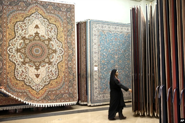 FILE - An Iranian female customer looks at the carpets in Tehran's old main bazaar,