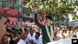 ທ່ານນາງ Aung San Suu Kyi ໂບກມືໃຫ້ບັນດາຜູ້ສະໜັບສະໜູນ ຢູ່ທີ່ສໍານັກງານແຫ່ງນຶ່ງ ທີ່ຫາກໍເປີດໃໝ່ ຂອງພັກສັນນິບາດແຫ່ງຊາດເພື່ອປະຊາທິປະໄຕຂອງທ່ານນາງ ທີ່ນະຄອນຢາງກຸ້ງ, ວັນທີ 17 ມັງກອນ 2012. (AP Photo/Khin Maung Win)