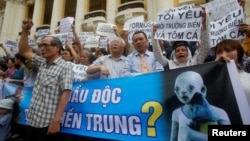 Demonstrators, holding signs to protest against Taiwanese enterprise Formosa Plastic and environmental-friendly messages, say they are demanding cleaner waters in the central regions after mass fish deaths in recent weeks, in Hanoi, Vietnam, May 1, 2016.