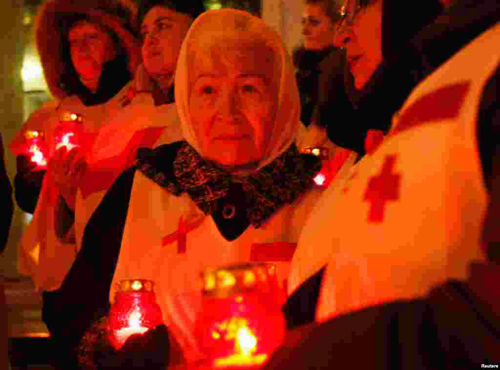 People hold candles as they mark the upcoming World AIDS Day in Kyiv, Ukraine, November 29, 2012.