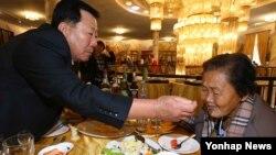 남북 이산가족 상봉행사 1회차 둘째날인 21일 금강산호텔에서 열린 공동중식에서 남측 박문수(71) 할아버지가 북측에서 온 누나 박문경(83) 할머니에게 음식을 먹여주고 있다.