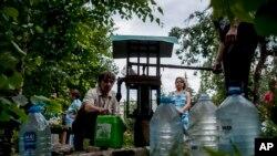 Şərqi Ukraynanın Slovyansk şəhərinin sakinləri su növbəsndə.