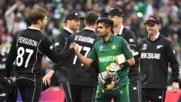 پاکستانی ٹیم کے کپتان بابر اعظم نیوزی لینڈ کی شکست کے بعد حریف کھلاڑی لاکی فرگوسن سے ہاتھ ملا رہے ہیں۔ فوٹو اے ایف پی