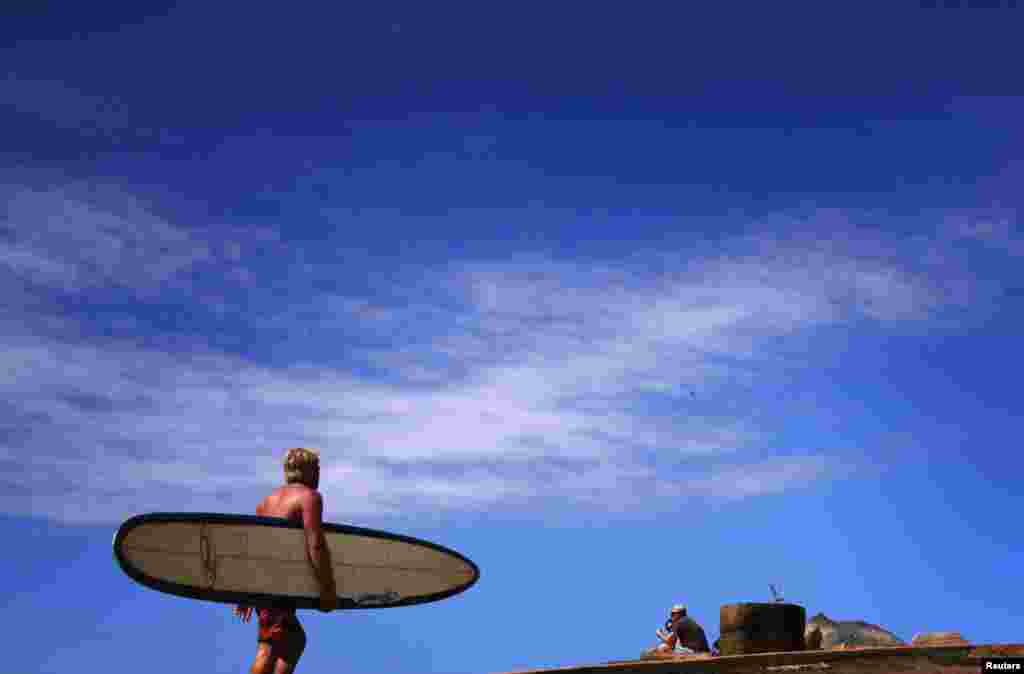 A surfer carrying his board walks towards the beach along a path at Long Reef Beach on a sunny day in Sydney, Australia.